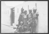 Small group of children standing outside of building.