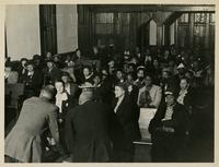 A crowd of men and women seated.