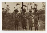 Four women carrying baskets on their heads.