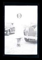 Nurse standing in front of cars.