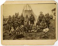 Group of men and children in front of tent.